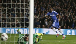 Chelsea's Samuel Eto'o, right, watches his shot go past Galatasaray's goalkeeper Fernando Muslera as he scores the opening goal during the Champions League last 16 second leg soccer match between Chelsea and Galatasaray at Stamford Bridge stadium in London, Tuesday, March 18, 2014. (AP Photo/Matt Dunham)