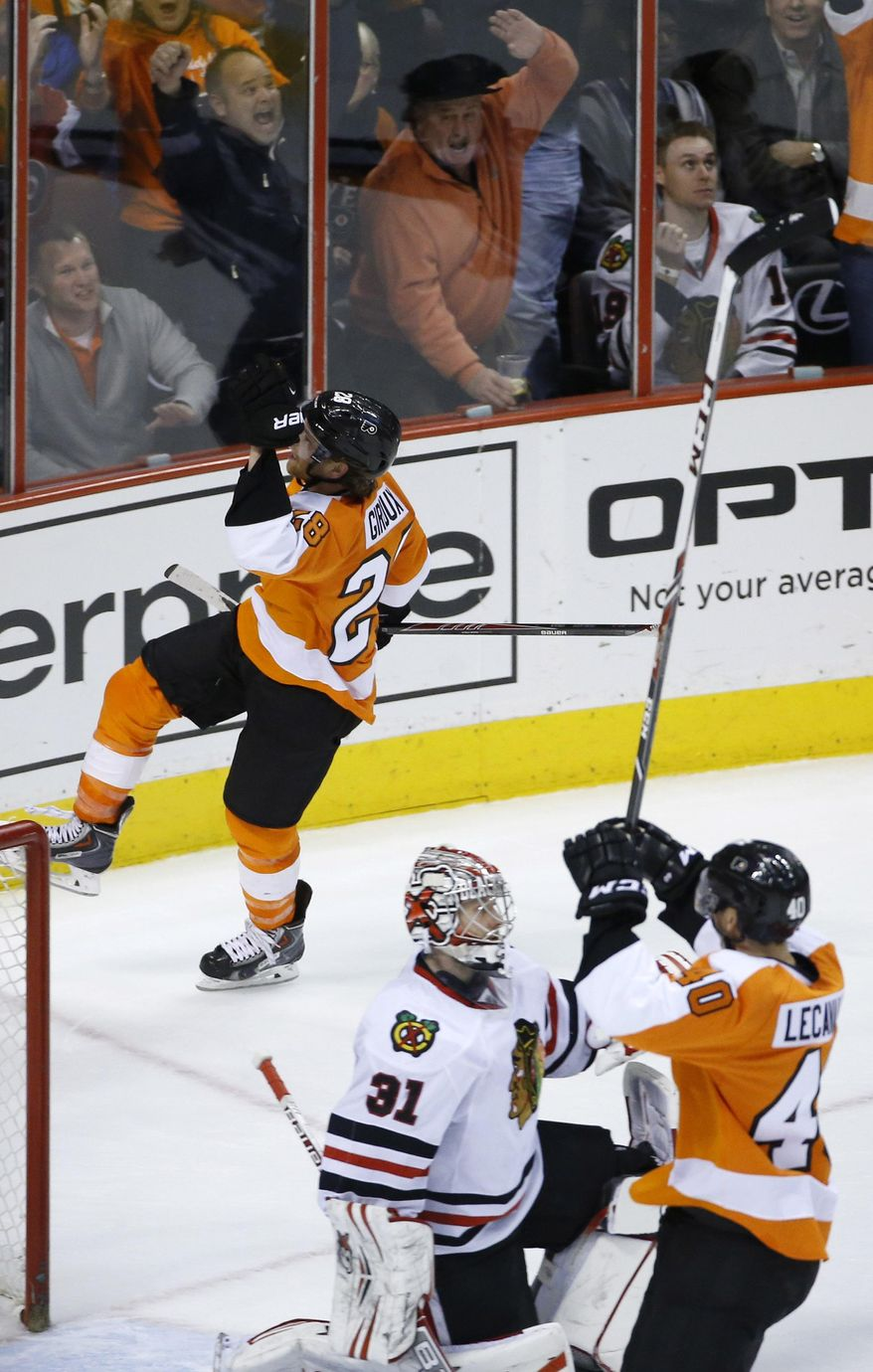 Philadelphia Flyers' Claude Giroux (28) and Vincent Lecavalier (40) celebrate after Giroux's goal against Chicago Blackhawks' Antti Raanta (31), of Finland, during overtime of an NHL hockey game, Tuesday, March 18, 2014, in Philadelphia. Philadelphia won 3-2. (AP Photo/Matt Slocum)