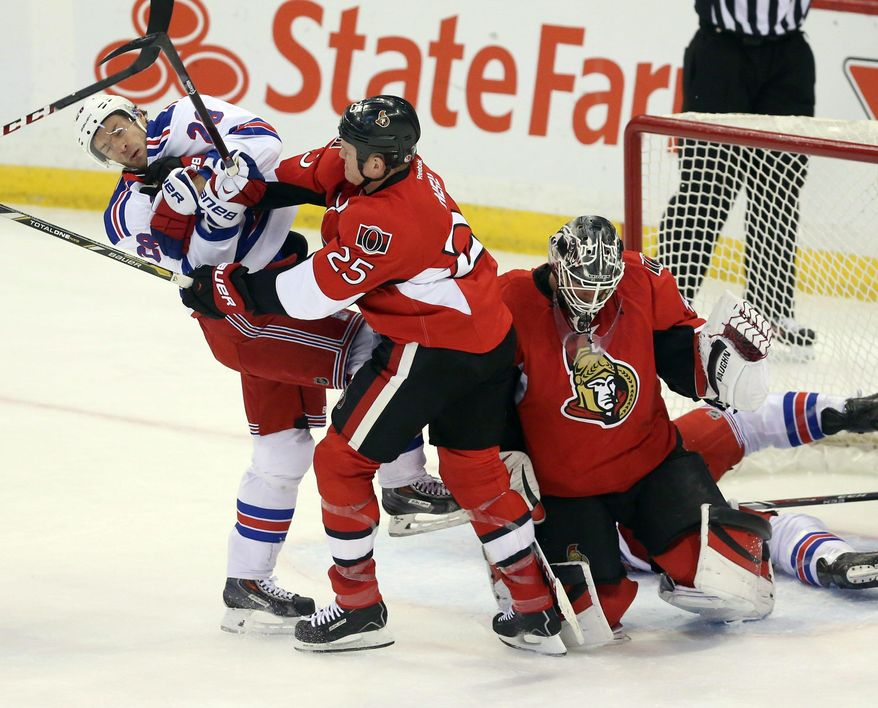 Ottawa Senators' Chris Neil (25) checks New York Rangers' Dominic Moore (28) as Senators goaltender Robin Lehner covers the puck during first period NHL hockey action in Ottawa, Ontario, Tuesday March 18, 2014.  (AP Photo/The Canadian Press, Fred Chartrand)