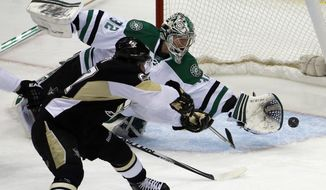 Pittsburgh Penguins' Sidney Crosby (87) backhands a shot past Dallas Stars goalie Kari Lehtonen (32) for a goal during the first period of an NHL hockey game in Pittsburgh, Tuesday, March 18, 2014. (AP Photo/Gene Puskar)
