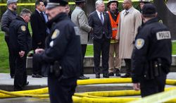 Seattle Mayor Ed Murray, center, visits the scene of a news helicopter crash in Seattle on Tuesday, March 18, 2014. A KOMO-TV helicopter helicopter crashed into a city street near Seattle's Space Needle, killing two people and critically injuring a person in a car on the ground. (AP Photo/The Seattle Times, Bettina Hansen)  SEATTLE OUT; USA TODAY OUT; MAGS OUT; TELEVISION OUT; NO SALES; MANDATORY CREDIT TO BOTH THE SEATTLE TIMES AND THE PHOTOGRAPHER