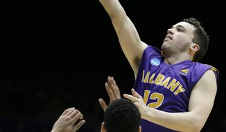 Albany guard Peter Hooley (12) drives against Mount St. Mary's guard Julian Norfleet (23) during the first half of a first-round game of the NCAA college basketball tournament, Tuesday, March 18, 2014, in Dayton, Ohio. (AP Photo/Al Behrman)