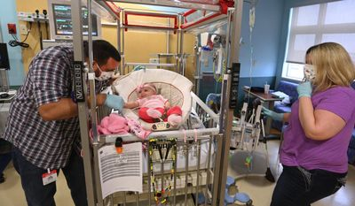Kevin and Priscilla Cervoni spend time with their 4 month-old daughter Mia, in her room at All Children's Hospital, St. Petersburg, Fla., on Feb. 21, 2014   Mia Cervoni is a patient and needs a heart transplant. (AP Photo/The Tampa Bay Times, Scott Keeler)
