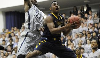 West Virginia guard Juwan Staten, right, goes to the basket against Georgetown forward Aaron Bowen (23) during the first half of an NCAA college NIT tournament first round basketball game, Tuesday, March 18, 2014, in Washington. (AP Photo/Nick Wass)