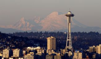 **FILE** Mount Baker is seen some 85 miles distant behind the Space Needle under clear skies at sunset on Nov. 21, 2013, in Seattle. (Associated Press)