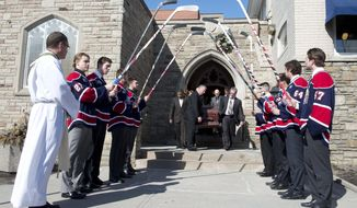 Saginaw Spirit hockey players hold up sticks as pall bearers carry out the coffin of teammate Terry Trafford after a funeral service in Toronto, Tuesday, March 18, 2014. The Toronto native's body was found last week in his SUV in a parking lot in Saginaw Township, Mich. (AP Photo/The Canadian Press, Frank Gunn)