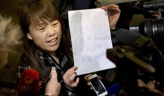 """A relative of a Chinese passenger aboard the missing Malaysia Airlines Flight MH370 shows a paper reading """"Hunger strike protest, Respect life, Return my relative, Don't want become victim of politics, Tell the truth"""" as she speaks to the media outside a hotel ballroom after attending a briefing held by airlines' officials in Beijing, China, Tuesday, March 18, 2014.  Families of the passengers aboard the missing plane decided to organize a hunger strike to express their anger and disappointment at the handling of the situation by authorities. They decided on the action after a daily morning meeting with two officials from Malaysia Airlines. The plane has been missing since March 8, and contradictory information plus the fact there has been no sign of the plane has left family  members frustrated. (AP Photo/Andy Wong)"""