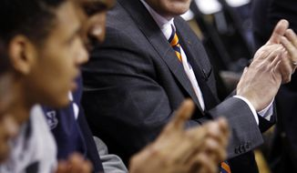 Auburn's new men's basketball coach, Bruce Pearl, sits with his players during his introduction, Tuesday, March 18, 2014, in Auburn, Ala. (AP Photo/Butch Dill)