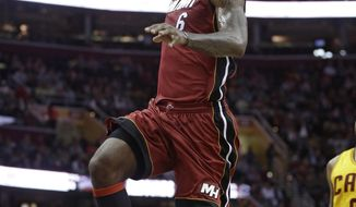 Miami Heat's LeBron James (6) jumps to the basket against the Cleveland Cavaliers during the first quarter of an NBA basketball game Tuesday, March 18, 2014, in Cleveland. (AP Photo/Tony Dejak)