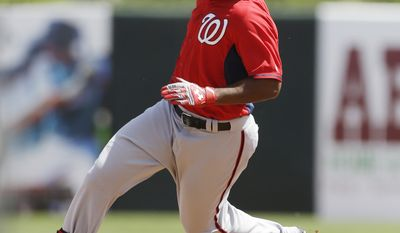 Washington Nationals' Brian Goodwin rounds second enroute to third during a spring exhibition baseball game against the Houston Astros in Kissimmee, Fla., Sunday, March 16, 2014. (AP Photo/Carlos Osorio)
