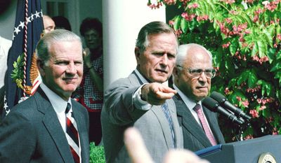 FILE - In this Aug. 20, 1991, file photo, President George H.W. Bush, flanked by  Secretary of State James Baker III, left, and U. S. Ambassador to the Soviet Union Robert Strauss, points to reporter during a Rose Garden press conference at the White House in Washington. Strauss, a former chairman of the Democratic Party and an ambassador to the Soviet Union, has died. Strauss' law firm confirmed his death Wednesday, March 19, 2014, at age 95. (AP Photo/Greg Gibson, File)