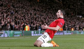 Manchester United's Robin van Persie celebrates scoring his side's third goal  and his hat-trick, during the Champions League, Round of 16, second leg match against Olympiakos,  at Old Trafford, Manchester,  England, Wednesday March 19, 2014. (AP Photo /PA, Peter Byrne) UNITED KINGDOM OUT
