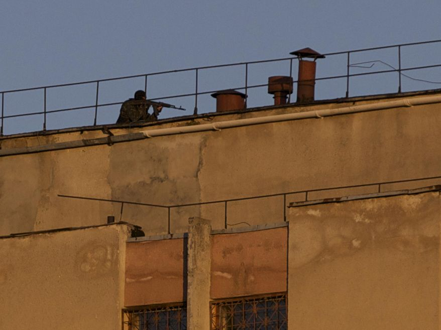 An armed man clears a roof of an Ukrainian military unit in Simferopol, Crimea, on Tuesday, March 18, 2014. (AP Photo/Ivan Sekretarev)