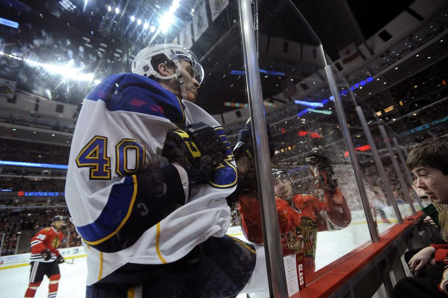 St. Louis Blues' Maxim Lapierre (40), and Chicago Blackhawks' Nick Leddy (8), run into the glass during the first period of an NHL hockey game in Chicago, Wednesday, March, 19, 2014. (AP Photo/Paul Beaty)