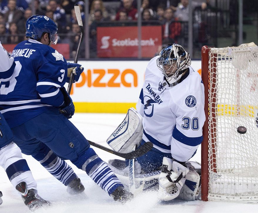 Tampa Bay Lightning goaltender Ben Bishop covers the post as Toronto Maple Leafs defenseman Dion Phaneuf looks for a rebound during second period NHL action in Toronto on Wednesday, March 19, 2014.  (AP Photo/The Canadian Press, Frank Gunn)