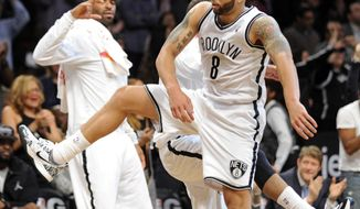 Brooklyn Nets' Deron Williams (8) celebrates with teammates as he comes back to the bench during the fourth quarter of an NBA basketball game against the Charlotte Bobcats Wednesday, March 19, 2014, at Barclay's Center in New York. Brooklyn won 104-99. (AP Photo/Bill Kostroun)