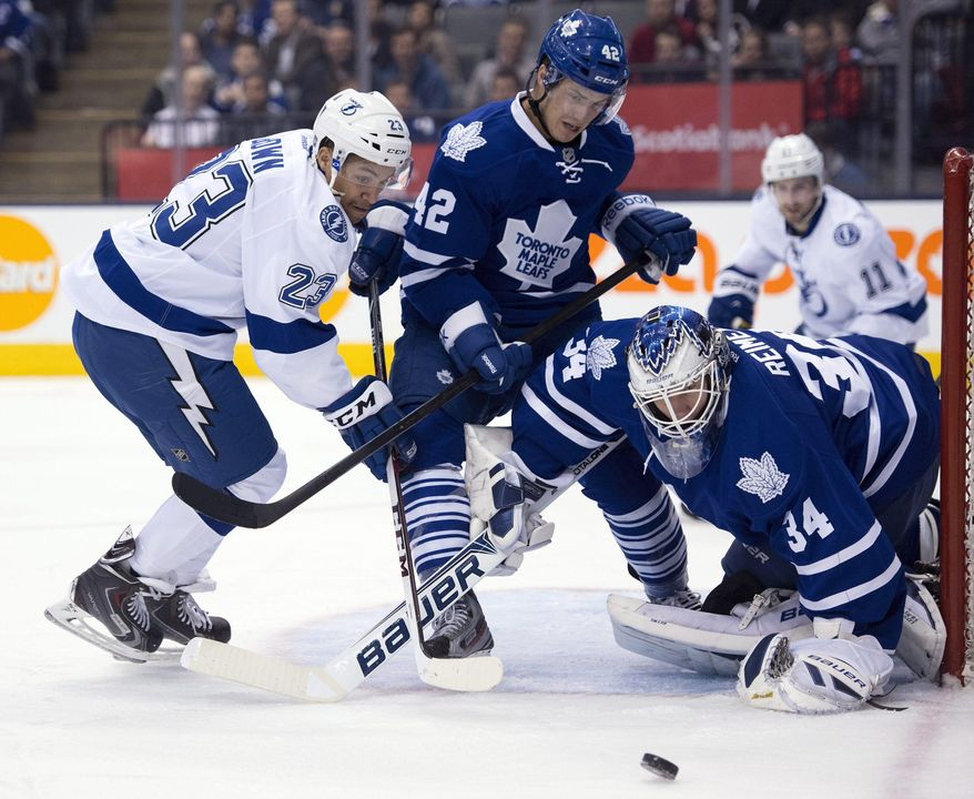 Toronto Maple Leafs center Tyler Bozak (42) holds off Tampa Bay Lightning right winger J.T. Brown (23) as goaltender James Reimer makes a save during first period NHL action in Toronto on Wednesday March 19, 2014. (AP Photo/The Canadian Press, Frank Gunn)