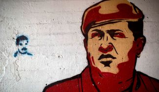 Images of the late Venezuelan President Hugo Chavez (right) and current President Nicolas Maduro cover a wall in downtown Caracas. Mr. Maduro, the hand-picked successor of Chavez, has remained popular among the working class but has failed to win the support of the discontented middle class. (Associated Press)