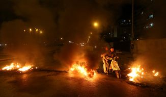 Lebanese citizens ride their scooter between burning tires that were set on fire by Sunni protesters, at one of the major roadways between Beirut and the capital's southern suburbs, a Hezbollah stronghold, to show their support with Sunni town of Arsal, in Beirut, Lebanon, Tuesday, March 18, 2014. Gunmen from Lebanon's militant Hezbollah group and local Shiite Muslim residents tightened their blockade of a Sunni town of Arsal near the Syrian border Tuesday, sparking concerns that thousands of Syrian refugees stranded in the area could be cut off from humanitarian aid. (AP Photo/Hussein Malla)