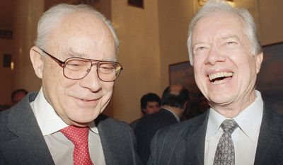 FILE - In this Nov. 10, 1992, file photo, former President Jimmy Carter shares a big laugh with departing American ambassador Robert Strauss at a reception at the envoy's residence in Moscow.  Strauss, a former chairman of the Democratic Party and an ambassador to the Soviet Union, has died. Strauss' law firm confirmed his death Wednesday, March 19, 2014, at age 95.(AP Photo/Liu Heung Shing, File)