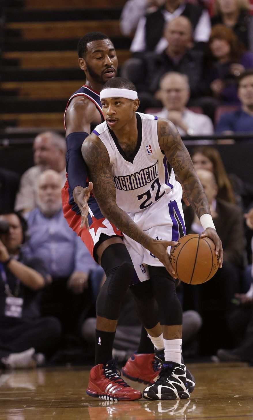 Sacramento Kings guard Isaiah Thomas, right, looks to pass against Washington Wizards guard John Wall during the first quarter of an NBA basketball game in Sacramento, Calif., Tuesday, March 18, 2014.(AP Photo/Rich Pedroncelli)