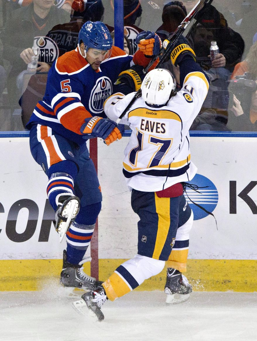 Nashville Predators' Patrick Eaves (17) checks Edmonton Oilers' Mark Fraser (5) during the first period of an NHL hockey game Tuesday, March 18, 2014, in Edmonton, Alberta. (AP Photo/The Canadian Press, Jason Franson)