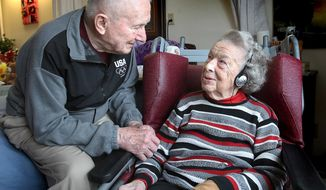 ADVANCE FOR RELEASE MONDAY, MARCH 24, 2014, AND THEREAFTER- In this March 17, 2014 photo, Ralph Schwanbeck sits with his wife Dorothy as she listens to music on an iPod at the Hillview Health Care Center in La Crosse, Wis. Hillview is one of 100 nursing homes in the state certified for the Wisconsin Music and Memory Initiative, which employs iPods with personalized playlists to rekindle residents' memories with familiar music, as well as lift their spirits and improve their interaction with family members, other residents and staffers. (AP Photo/The La Crosse Tribune, Erik Daily)