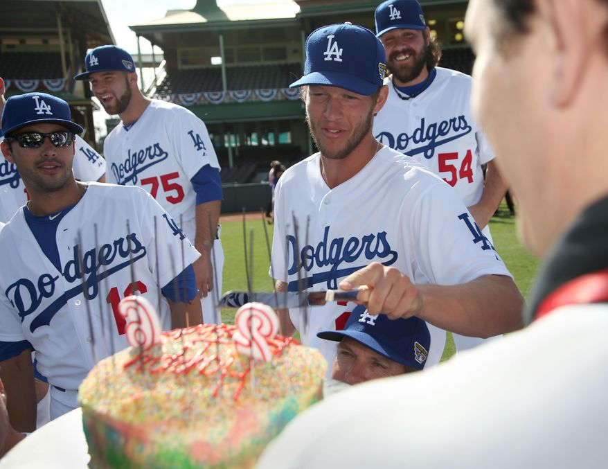 The Los Angeles Dodgers' Clayton Kershaw, third right, is presented with a birthday cake at she Sydney Cricket Ground in Sydney, Wednesday, March 19, 2014. The MLB season-opening two-game series between the Los Angeles Dodgers and Arizona Diamondbacks in Sydney will be played this weekend. (AP Photo/Rick Rycroft)