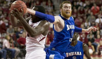 Indiana State forward Justin Gant, right, reaches around for a steal against Arkansas forward Alandise Harris, left, during the second half of an opening round National Invitational Tournament NCAA college basketball game in Fayetteville, Ark., Tuesday, March 18, 2014. Arkansas defeated Indiana State 91-61.(AP Photo/Gareth Patterson)