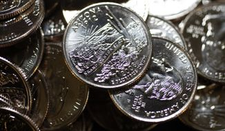 Coins from the initial run of the Arizona quarter fall into a catch bin below the press during a ceremony at the U.S. Mint in Denver on Friday, May 16, 2008. The Arizona quarter, which features an image of the Grand Canyon with a Saguaro cactus in the foreground, is the 48th coin in the U.S. Mint's 50 State Quarters program and the third commemoriative quarter-dollar coin released in 2008. Alaska and Hawaii coins are scheduled for production later this year to round out the programs. (AP Photo/David Zalubowski)