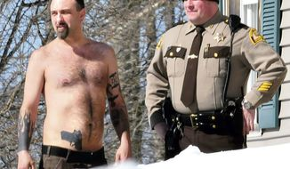 "Michael Smith (left) stands beside a Somerset County Sheriff deputy outside his home in Norridgewock, Maine, on March 18, 2014. Officers armed with assault rifles descended on Smith's home after members of a tree removal crew he'd told to clear off his property reported that he had a gun. The ""gun"" the tree crew had seen on Smith actually was a life-sized tattoo of a handgun on his stomach. (Associated Press/Morning Sentinel, David Leaming)"