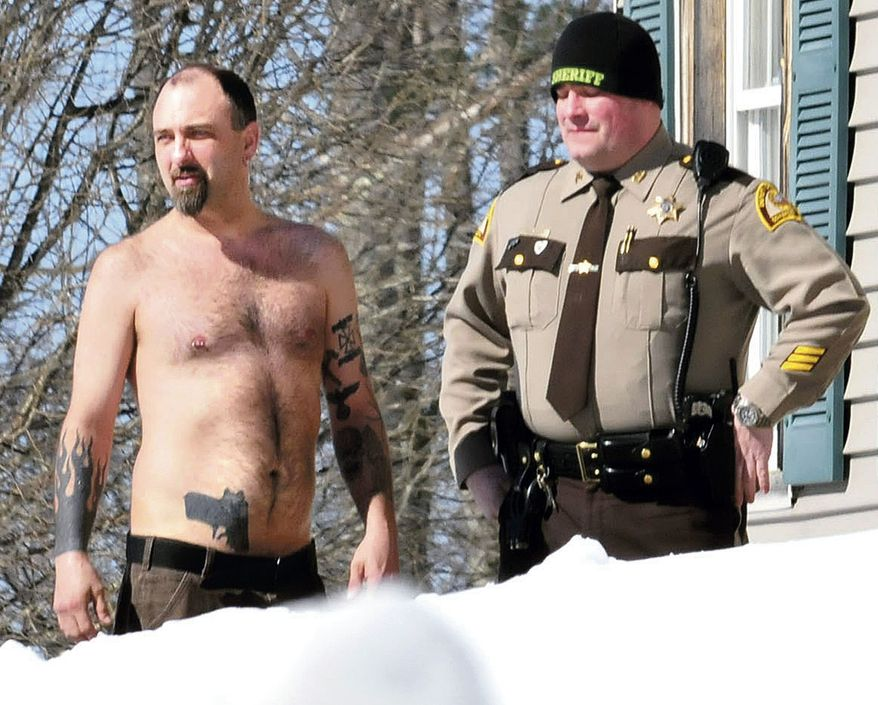 """Michael Smith (left) stands beside a Somerset County Sheriff deputy outside his home in Norridgewock, Maine, on March 18, 2014. Officers armed with assault rifles descended on Smith's home after members of a tree removal crew he'd told to clear off his property reported that he had a gun. The """"gun"""" the tree crew had seen on Smith actually was a life-sized tattoo of a handgun on his stomach. (Associated Press/Morning Sentinel, David Leaming)"""