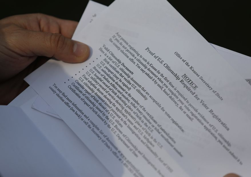**FILE** Aaron Belenky shows part of a letter from election officials while standing in front of his apartment in Overland Park, Kan., on Aug. 14, 2013. The letter lists the valid citizenship documents needed to register to vote in Kansas for the first time. Belenky allowed the American Civil Liberties Union to list him as one of three aggrieved voters in a notice sent this week to Kansas Secretary of State Kris Kobach. (Associated Press)