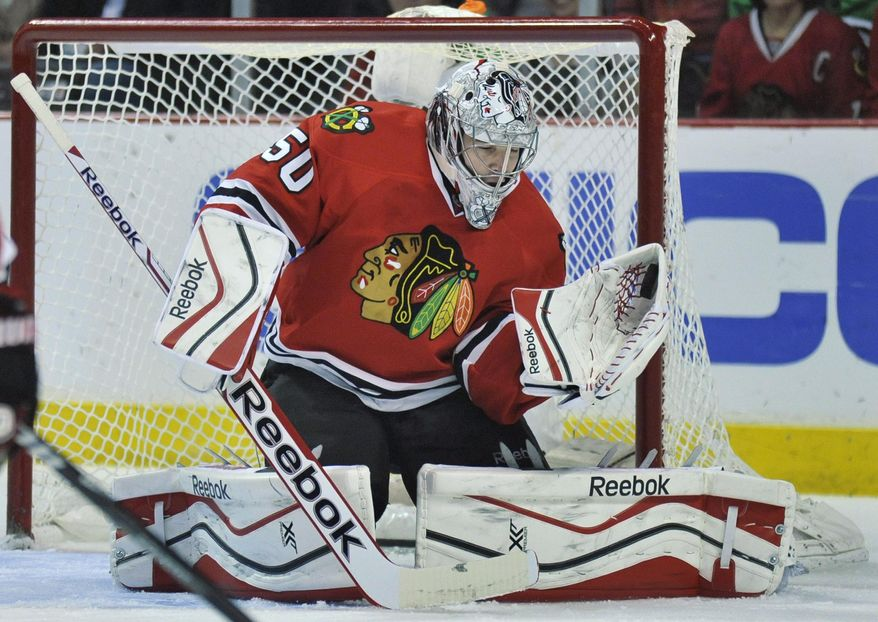 Chicago Blackhawks goalie Corey Crawford makes a save during the first period of an NHL hockey game against the St. Louis Blues in Chicago, Wednesday, March, 19, 2014. (AP Photo/Paul Beaty)