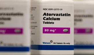 FILE - This 2011 photo provided by Watson Pharmaceuticals Inc. shows bottles of Atorvastatin Calcium tablets, a generic form of Lipitor which is sold under a deal with Pfizer. Half of Americans ages 40 to 75 and nearly all men over 60 qualify to consider cholesterol-lowering statin drugs under heart disease prevention guidelines issued in November 2013, a new analysis concludes. It was published online Wednesday, March 19, 2014 by the New England Journal of Medicine. (AP Photo/Watson Pharmaceuticals Inc., Bill Gallery)