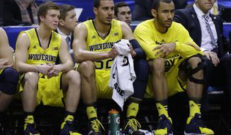 Michigan's Spike Albrecht, left, Jordan Morgan, center, and Jon Horford watch from the bench in the second half of an NCAA college basketball game against Michigan State in the championship of the Big Ten Conference tournament on Sunday, March 16, 2014, in Indianapolis. Michigan State won 69-55. (AP Photo/Michael Conroy)