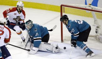 Florida Panthers' Brandon Pirri (73) scores past San Jose Sharks goalie Antti Niemi (31), of Finland, and defenseman Scott Hannan (27) during the second period of an NHL hockey game on Tuesday, March 18, 2014, in San Jose, Calif. (AP Photo/Marcio Jose Sanchez)
