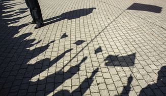 ** FILE ** In this Tuesday, March 18, 2014, file photo, people cast shadows waving flags as they gather at a square to watch a televised address by Russian President Vladimir Putin to the Federation Council, in Sevastopol, Crimea. (AP Photo/Andrew Lubimov, File)