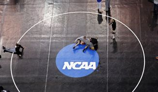 Donald Patrick, left, of Davidson College in Davidson, N.C., works with his coach, Brandon Sinnott, right, on a wrestling mat in Oklahoma City, Wednesday, March 19, 2014, in preparation for the NCAA college wrestling championships. Competition begins March 20. (AP Photo/Sue Ogrocki)