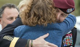 In this photo taken on Monday, March 17, 2014, Brig. Gen. Jeffrey Sinclair embraces his defense attorney Ellen C. Brotman outside the Fort Bragg, N.C. courthouse. Lawyers for Sinclair, an Army general who admitted to emotionally harming a subordinate during an affair, will argue Tuesday, March 18, 2014,  he shouldn't face jail time for a crime that civilians wouldn't be prosecuted for.  (AP Photo/The Fayetteville Observer, Johnny Horne)