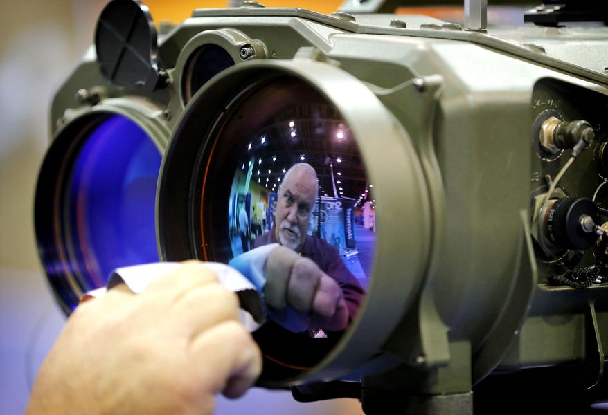 Gary Wagner, of Elbit Systems of America, cleans the lens of a long range thermal imaging targeting system at the 8th annual Border Security Expo, Tuesday, March 18, 2014 in Phoenix. The two day event will feature panel discussions, sharing intelligence, and exhibitors displaying high-tech wares aimed at securing lucrative government contracts and private sales. (AP Photo/Matt York)