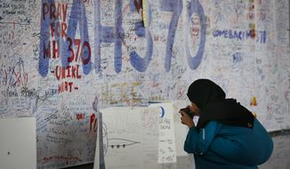 A woman takes picture in front of  messages board for the passengers aboard a missing Malaysia Airlines plane at Kuala Lumpur International Airport in Sepang, Malaysia, Wednesday, March 19, 2014. New radar data from Thailand gave Malaysian investigators more potential clues Wednesday for how to retrace the course of the missing Malaysian airliner, while a massive multinational search unfolded in an area the size of Australia. (AP Photo/Vincent Thian)