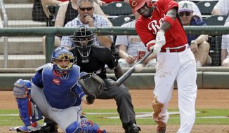 Cincinnati Reds' Brandon Phillips hits a solo home run off Texas Rangers pitcher Robbie Ross in the fifth inning of a spring exhibition baseball game Thursday, March 20, 2014, in Goodyear, Ariz. (AP Photo/Mark Duncan)