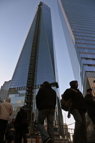 FILE. - This Feb. 11, 2014 file photo shows pedestrians in front of the 1 World Trade Center building, left, in New York. A 16-year-old boy from Weehawken, N.J., is accused of bypassing security in the middle of the night and climbing a ladder to the spire of 1 World Trade Center to take pictures according the the Port Authority of New York and New Jersey. The teen was arrested on the premises at 6 a.m. Sunday March 16, 2014 and his camera and cellphone were seized after authorities obtained a search warrant. He was later released without bail. (AP Photo/Bebeto Matthews, File)