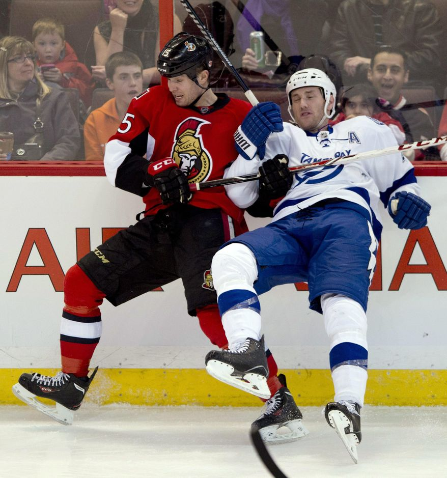 Ottawa Senators center Zack Smith, left, collides with Tampa Bay Lightning defenseman Eric Brewer along the boards during the second period of an NHL hockey game Thursday, March 20, 2014, in Ottawa, Ontario. (AP Photo/The Canadian Press, Adrian Wyld)
