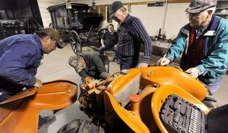 ADVANCE FOR USE MONDAY, MARCH 24, 2014, AND THEREAFTER- In this March 17, 2014 photo, members of the Friends of Gus Pruser Agriculture Exhibit take apart an Allis Chalmers G tractor at the Gus Pruser Agriculture Exhibit at the Z.I. Hale Museum. in Winters, Texas. (AP Photo/The Abilene Reporter-News, Ronald W. Erdrich)