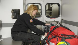 ADVANCE FOR SUNDAY, MARCH 23 - In this photo taken on March 13, 2014, Caylee Knafel, a senior at Churubusco High School, checks the monitor in a Huntertown Fire Department ambulance in Huntertown, Indiana.  Knafel is part of an internship that helps to train volunteers for the department. (AP Photo/The Journal-Gazette, Michele Davies)  NEWS-SENTINEL OUT; MANDATORY CREDIT; NO SALES; MAGS OUT