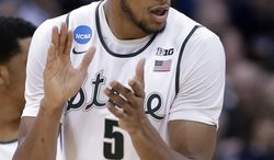 Michigan State's Adreian Payne claps his hands together after hitting a 3-point shot against Delaware in the first half during the second round of the NCAA men's college basketball tournament in Spokane, Wash., Thursday, March 20, 2014. (AP Photo/Elaine Thompson)