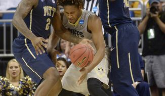 Pittsburgh forwards Michael Young (2), left, and Talib Zanna (42), right,  defend Colorado forward Xavier Johnson (2) as he loses control of the ball during the first half in a second-round game in the NCAA college basketball tournament Thursday, March 20, 2014, in Orlando, Fla. (AP Photo/Phelan M. Ebenhack)
