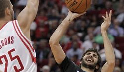 Minnesota Timberwolves guard Ricky Rubio (9) shoots as Houston Rockets forward Chandler Parsons (25) defends during the second quarter of an NBA basketball game, Thursday, March 20, 2014, in Houston. (AP Photo/Patric Schneider)